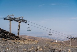 Hike in the mountains of Sierra Nevada for winter sports. Leisure and winter sports, passenger chairlift in the ski resort.