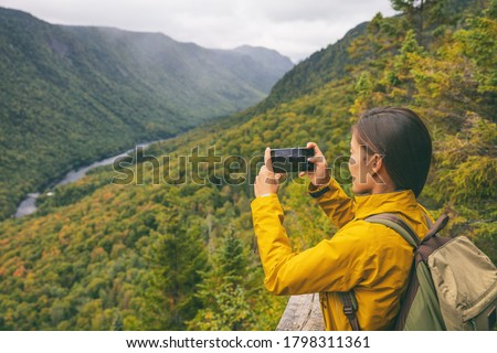 Hike woman hiker taking picture with phone of river view from top of trail hiking in Parc National de la Jacques Cartier, Quebec, Canada autumn travel camping lifestyle. Photo stock ©