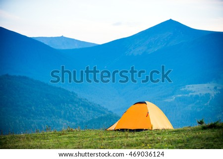 hike yellow tent on the background of mountains, daytime, space #469036124
