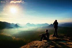 Hiker and photo enthusiast stay with tripod on cliff and thinking. Dreamy fogy landscape, blue misty sunrise in a beautiful valley below, soft focus