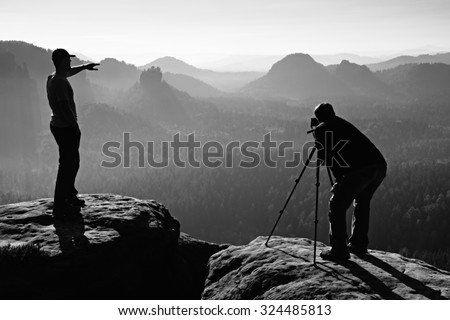 Hiker and photo enthusiast stay with tripod on cliff and thinking. Dreamy fogy landscape, blue misty sunrise in a beautiful valley below. Black and white photo