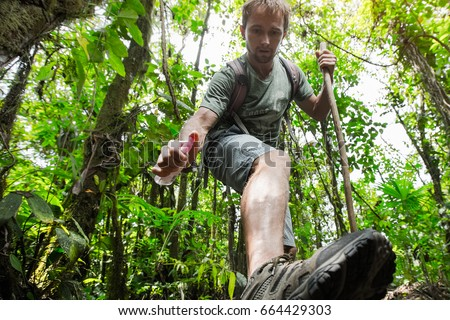 Hiker applying repellent on his leg in dense tropical forest