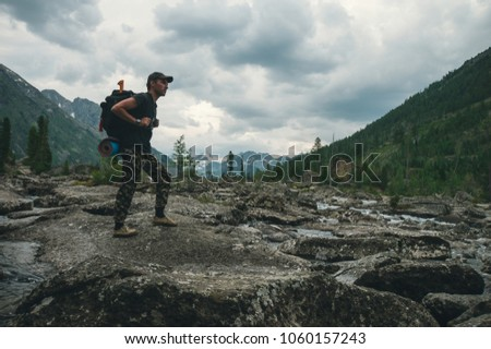 hiker ascenting in a mountains. Tourist with a large backpack the evening sneaking through the stone deposits on the mountainside. #1060157243