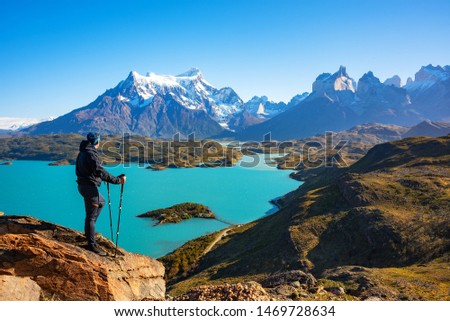 Photo of  Hiker at mirador condor enjoying amazing view of Los Cuernos rocks and Lake Pehoe in Torres del Paine national park, Patagonia, Chile