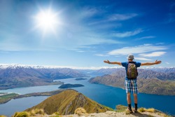 hiker at the top his hands raised enjoy sunny day. New Zealand