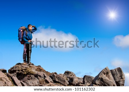 hiker at the top of a rock enjoy sunny day