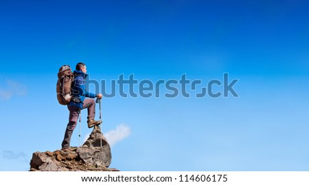 hiker at the top of a rock with backpack enjoy sunny day