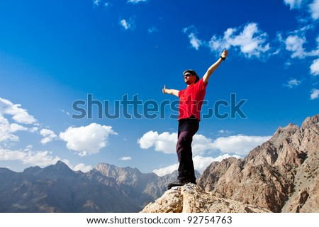 hiker at the top of a rock with his hands up