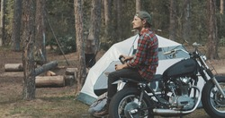 Hiker biker camping in forest. Handsome guy sits on motorcycle and drinks hot beverage from thermos in woods.