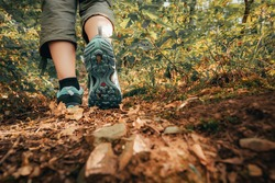 Hiker boots footsteps on muddy ground. Sole of shoe in motion on track. Walking hike. Close-up of woman traveler feet.