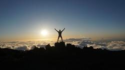 Hiker celebrates meeting beautiful sunset at a mountain peak above clouds at Haleakala Volcano in Maui, Hawaii