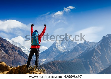 Hiker cheering elated and blissful with arms raised in the sky after hiking. Everest base camp trek #425598697