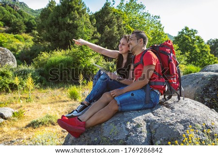 Hiker couple looking at tablet sitting on a rock and pointing a finger in one direction