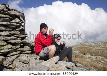 Hiker couple taking pictures up in the mountains