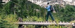 Hiker crossing a bridge on a trail