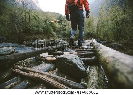 Hiker crossing the bridge in Himalayas. Hiking the Himalayas