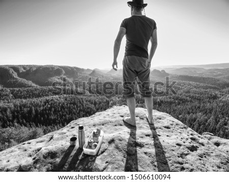 Hiker enjoy Refreshment. Tourist staying on top of Rock and enjoying Mountain View