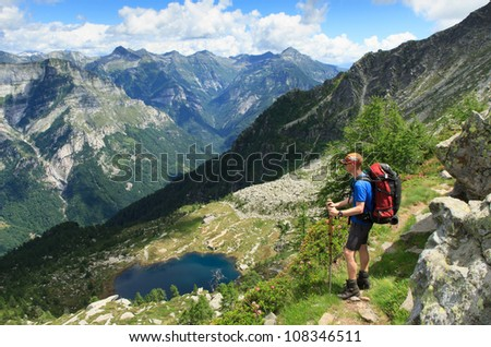 Hiker enjoying the view near a lake in the mountains.