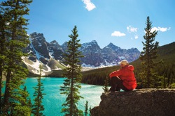 Hiker enjoying the view of Moraine lake in Banff National Park, Alberta, Canada, with snow-covered peaks of canadian Rocky Mountains in the background.