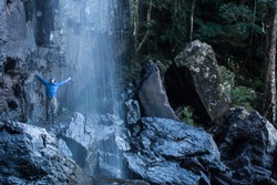 Hiker Enjoys Standing in a Waterfall
