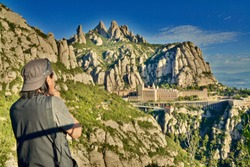 Hiker Enjoys the Spirituality Mountainview Above the Montserrat Abbey. Spectacular Views of Catalan's landscape. Benedictine monastery of Santa Maria de Montserrat is 45 km north of Barcelona, Spain