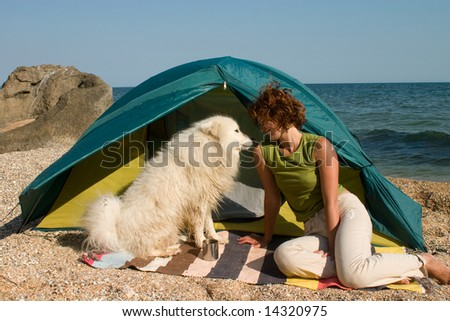 hiker girl and samoyed dog near of tent