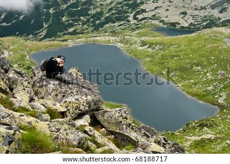 Hiker girl in Retezat mountain,siting on a rock above Bucura lake - stock photo