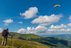 Hiker girl on the mountain top looks at the blue sky with soaring paraglider wing. Amazing vacation in the mountains. Borzhava ridge, Ukraine.