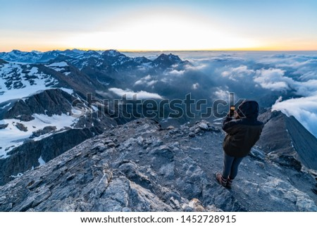 Hiker girl stands on the peak of sandstone rock in Alps mountain watching to Sun rise. Beautiful moment the miracle of nature with clouds, peaks and glacier