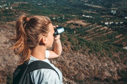 Hiker girl with backpack looking in binoculars enjoying spectacular view of valley on mountain top. Wild adventure. Young watcher tourist in travel in nature observes the landscape. Hiking alone