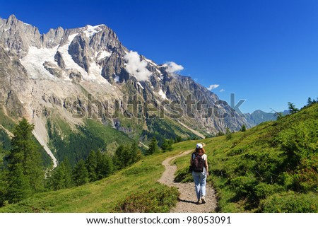 hiker in action in Ferret valley with Mont Blanc massif on background
