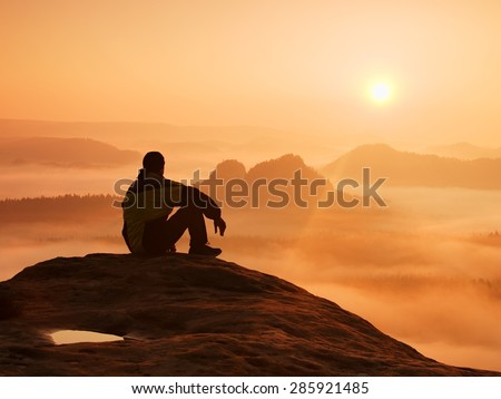 Hiker in black on the rocky peak. Wonderful daybreak in mountains, heavy orange mist in deep valley. Man sit on the rock and watch over the fog .
