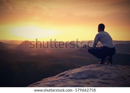 Hiker in black sit alone on the rock summit. Wonderful daybreak in mountains, heavy mist in deep valley. Man sit on the rock.