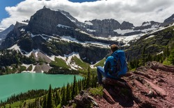 Hiker in glacier national park enjoying the view of Grinnell lake