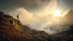Hiker in mountains with a backpack and trekking poles rejoices at the top during a beautiful sunset in the Himalayas. Nepal.Travel and adventure sport lifestyle concept.