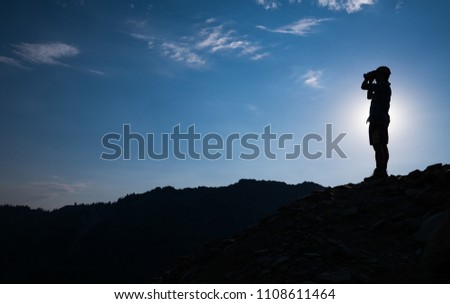 Hiker in silhouette scans horizon with binoculars