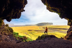 Hiker in the Loftsalahellir Cave near the village of Vik overlooking the beautiful landscape of Iceland with a road passing by.