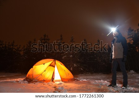 hiker is stand near tent in night winter forest