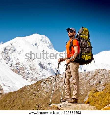Hiker is standing on cliff and looks at Himalaya mountains