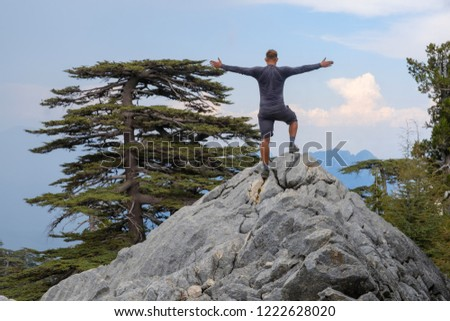 Hiker is standing on peak of rocks and looks into valley of the cherished Lebanese cedars. Turkey. Lycian path. Tahtal Dag