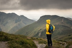Hiker looking at cloudy sky over mountain range. Woman hiking in mountains during bad weather. Adventure in nature