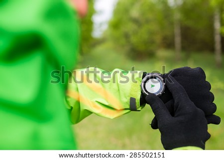 Hiker looking at electronic compass, sport gps smart watch. Man checking direction on smartwatch, navigation equipment. Hiking healthy sport and fitness outdoors in nature.