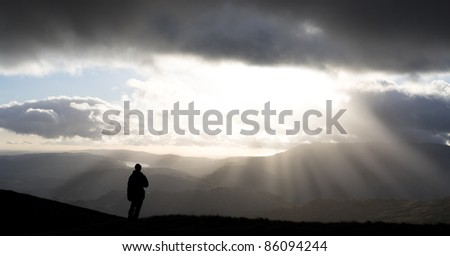 Hiker looking at scenic view as sun bursts through clouds, Lake District, England