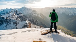 Hiker looking at view on mountain top summit on hiking travel vacation. Wanderlust adventure people relaxing. Summit of famous hike to Serles, Stubai, Austria. Sunset or sunrise