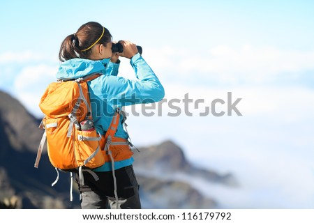 Hiker looking in binoculars enjoying spectacular view on mountain top above the clouds. - stock photo