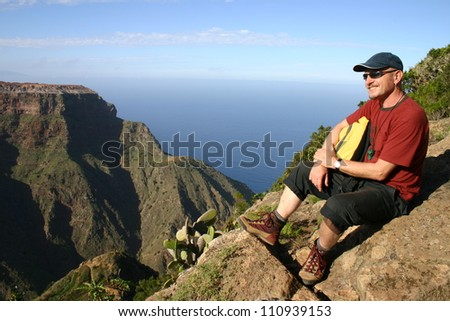 Hiker looking out to sea from a cliff on island of La Gomera, Canary Islands