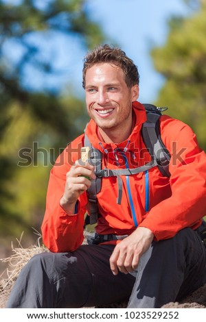 Hiker man healthy outdoor lifestyle eating muesli bar during hike on mountain hiking. Happy people eat granola cereal bar snack living active lifestyle in nature.