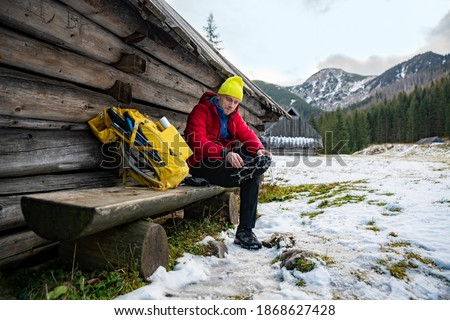 Hiker man in a yellow cap and a red down jacket sits on a wooden bench and puts crampons on his boots. The yellow backpack is lying next to the tourist. Photo stock ©