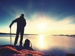 Hiker man in dark sportswear and with sporty backpack on rocky coast. Backpacker in water mirror stand on boulder and enjoy sunset at horizon with blue sky with clouds. Magic day.