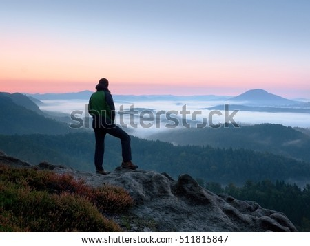 Hiker  man on rock watch over valley and foggy morning landscape. Beautiful fall morning. Autumn hilly cvountryside #511815847